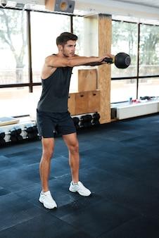 Fitness-mann hält das gewicht. aufgaben machen