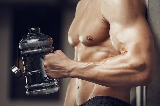Fitness-mann im trinkwasser des fitnessraums nach dem training. fitness und bodybuilding. kaukasischer mann, der übungen im fitnessstudio macht.