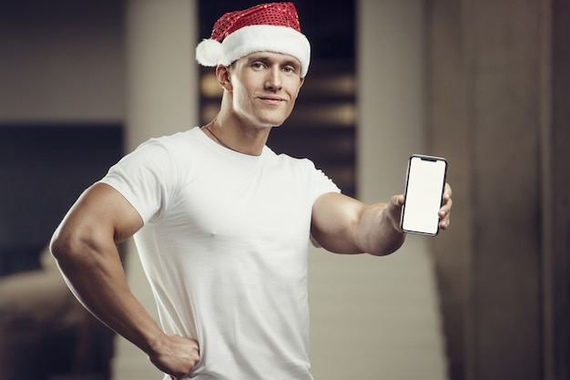 Fitness-mann im weihnachtsmannhutkostüm im fitnessstudio mit handy. frohe weihnachten und neujahr konzept