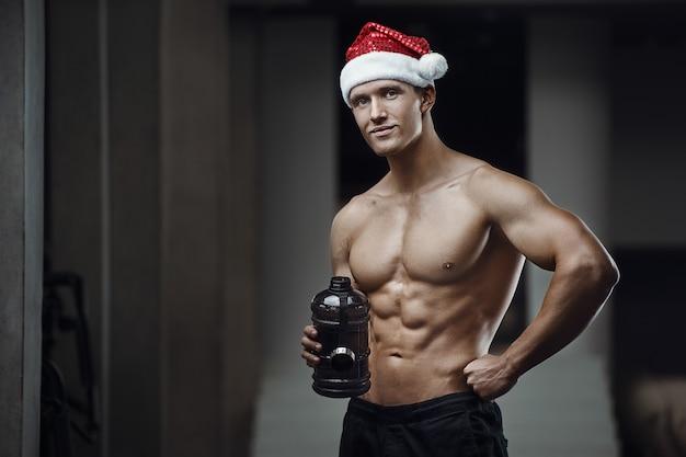 Fitness-mann im weihnachtsmannhutkostüm im fitnessstudio.
