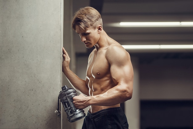 Fitness-mann in der turnhalle trinkwasser nach dem training auf handy