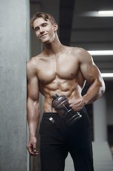 Fitness-mann in der turnhalle trinkwasser nach dem training mit blick auf handy