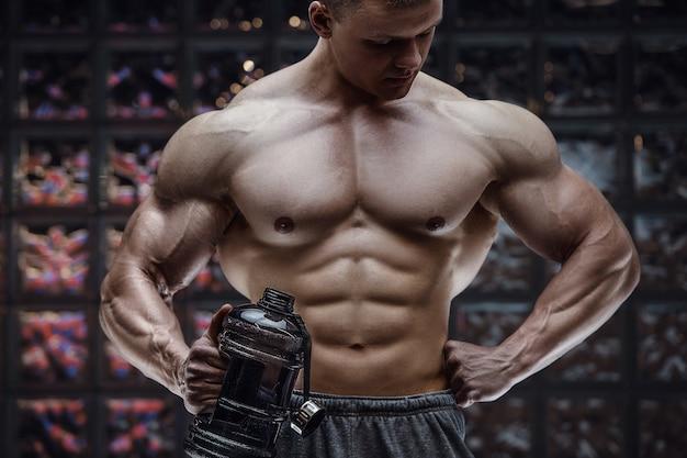 Fitness-mann in der turnhalle trinkwasser nach dem training