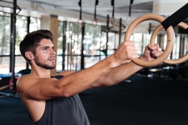 Fitness-mann klammert sich an den ring im fitnessstudio. im profil