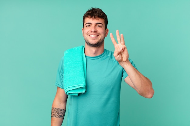 Fitness-mann lächelt und sieht freundlich aus, zeigt nummer drei oder dritte mit der hand nach vorne und zählt herunter