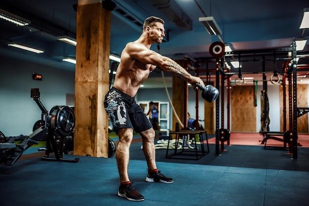 Fitness-mann schwingt kettlebells im fitnessstudio