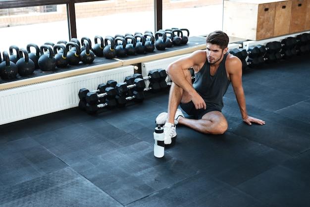 Fitness-mann sitzt im fitnessstudio. mit flasche. sich hinsetzen