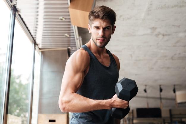 Fitness-mann steht seitlich im fitnessstudio. nach vorne schauen. mit hantel