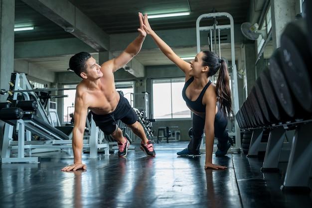Fitness mann und frau machen liegestütze nach dem training, fit paar high five nach dem training im club gym.