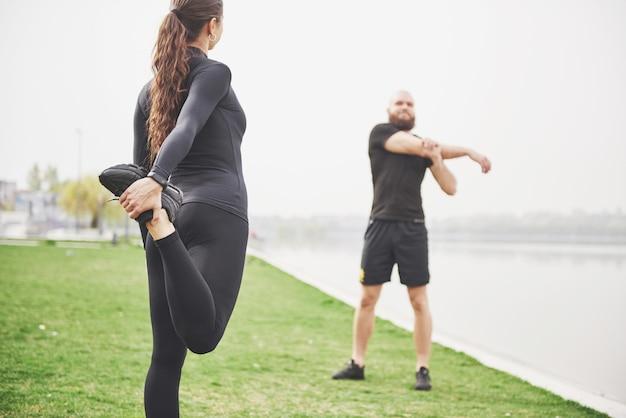 Fitness-paar, das draußen im park nahe dem wasser streckt. junger bärtiger mann und frau, die zusammen am morgen trainieren