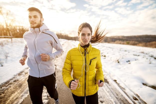 Fitness-paar in der wintersportbekleidung, die in der verschneiten natur mit kopfhörern läuft.