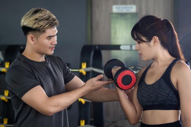 Fitness personal trainer beraten eine frau für das körperliche training.