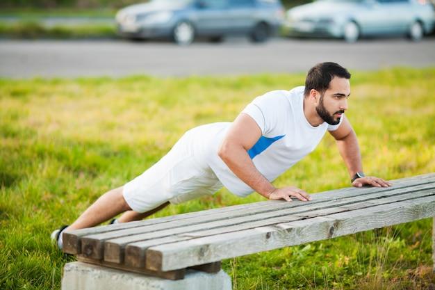Fitness. push-up-übungseignungsmanntraining bewaffnet muskeln turnhalle an der im freien