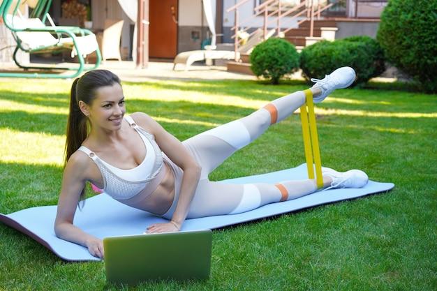 Fitness schöne schlanke frau macht seitliche planke mit widerstandsband und sieht sich online-tutorials auf dem laptop an, trainiert im freien.