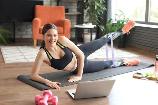 Fitness schöne schlanke frau macht seitliche planke mit widerstandsband und sieht sich online-tutorials auf dem laptop an, trainiert im wohnzimmer. bleiben sie zu hause aktivitäten.