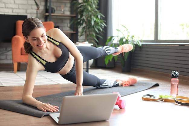 Fitness schöne schlanke frau macht side plank und sieht sich online-tutorials auf dem laptop an, trainiert im wohnzimmer. bleiben sie zu hause aktivitäten.