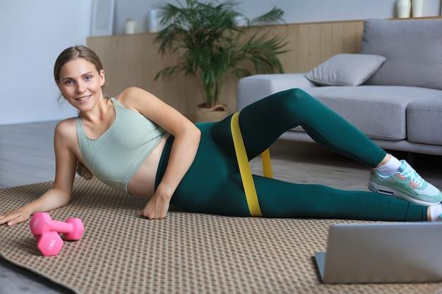 Fitness schöne schlanke frau macht übungen für die beine mit einem gummiband und schaut sich online-tutorials auf dem laptop an, trainiert im wohnzimmer. bleiben sie zu hause aktivitäten.