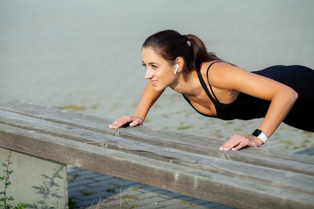 Fitness. schönes junges mädchen mit perfekten muskeln. sie trainiert die rückenmuskulatur. concept-power beauty diät sport
