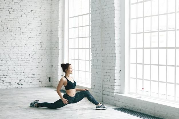 Fitness-, sport-, energie-, gesundheits- und aktivitätskonzept. bild des fröhlichen athletischen mädchens in den stilvollen turnschuhen, im oberteil und in den leggings, die drinnen trainieren und ihre beine vor großem fenster strecken