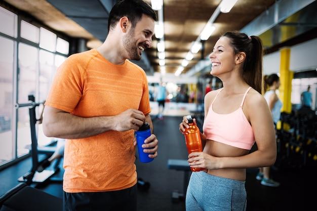 Fitness-, sport-, fitness- und gesundes lifestyle-konzept - gruppe glücklicher menschen im fitnessstudio