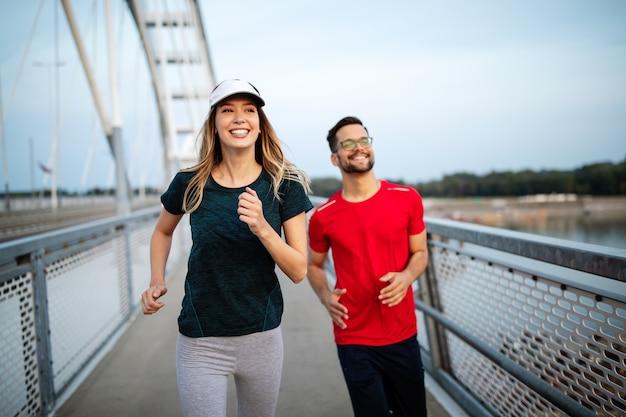 Fitness, sport, menschen, training und lifestyle-konzept. fittes paar läuft im freien
