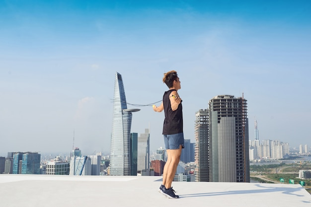 Fitness-, sport-, menschen-, trainings- und lifestyle-konzept - mann springt mit springseil im freien