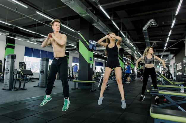 Fitness-, sport-, trainings-, fitness- und lifestyle-konzept - gruppe lächelnder menschen, die im fitnessstudio trainieren und kniebeugen machen