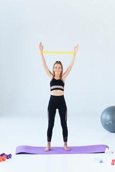 Fitness-, sport-, trainings-, menschen- und lifestyle-konzept - frau, die übungen mit expander oder widerstandsband im fitnessstudio macht