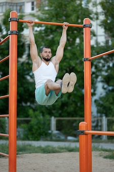 Fitness-, sport-, trainings-, trainings- und lifestyle-konzept - junger mann macht bauchmuskelübungen auf der reckstange im sommerpark