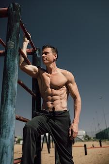 Fitness-, sport-, trainings- und lifestyle-konzept - junger mann, der am reck am strand trainiert. foto in hoher qualität