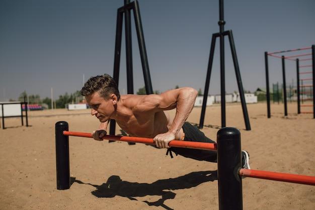 Fitness-, sport-, trainings- und lifestyle-konzept - junger mann, der im freien handstand an der bar ausübt - calisthenics. foto in hoher qualität