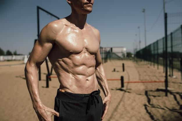 Fitness-, sport-, trainings- und lifestyle-konzept - junger mann mit schönem aufgepumptem körper, der am strand posiert. foto in hoher qualität