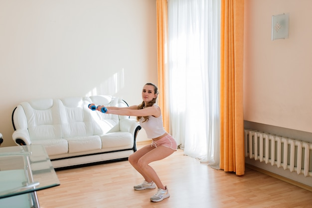 Fitness-, sport-, trainings- und lifestyle-konzept - lächelndes frauentraining zu hause