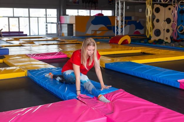 Fitness-, sport-, übungs-, dehnungs- und personenkonzept - lächelnde frau, die spalten auf matte über turnhallenhintergrund tut.