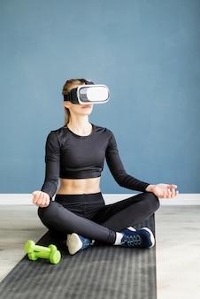 Fitness, sport und technik. junge athletische frau, die brille der virtuellen realität trägt, die yoga auf fitnessmatte tut