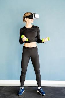 Fitness, sport und technik. junge athletische frau, die virtual-reality-brille steht, die an fitnessmatte steht, die mit dubbells arbeitet