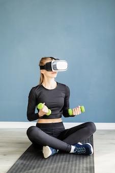 Fitness, sport und technik. junge athletische frau, die virtuelle realitätsbrillen sitzt auf fitnessmatte sitzt