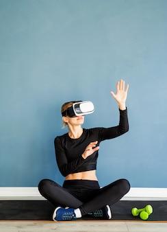 Fitness, sport und technik. junge athletische frau, die virtuelle realitätsbrillen sitzt, die an der fitnessmatte unter verwendung des interaktiven vr-menüs am blauen hintergrund sitzen
