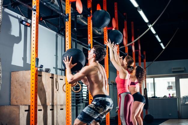 Fitness-, sport- und trainingskonzept - menschen mit medizinbällen trainieren im fitnessstudio