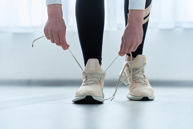 Fitness sportliche frau bindet schnürsenkel auf turnschuhen und macht sich bereit für laufen und training. sport treiben und fit sein. sportler mit gesundem sportlichem lebensstil