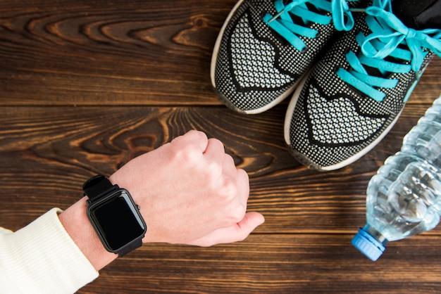 Fitness-tracker und turnschuhe mit wasserflasche
