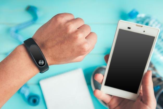 Fitness-tracker zur hand. turnschuhe, eine flasche wasser, maßband auf blau, flach liegen