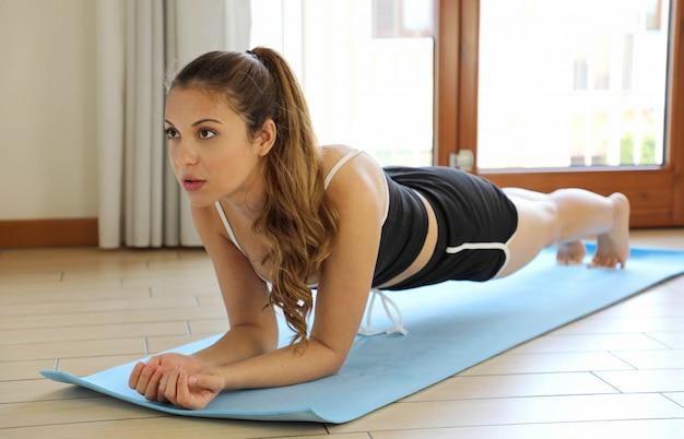 Fitness-training der jungen frau zu hause. mädchen, das plankenübungen macht, trainiert muskeln als teil eines gesunden lebensstils, ohne ins fitnessstudio zu gehen.