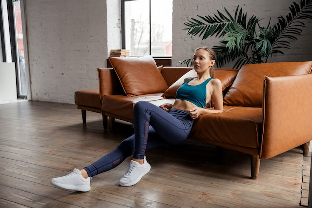 Fitness-training zu hause. gesunde fit junge frau, die trizeps-dips-übung im wohnzimmer am sofa tut.