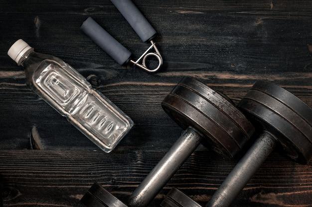Fitness-trainingsgeräte. dummkopf oder barbell auf einer bretterbodenoberfläche. flachlage entsättigtes konzept