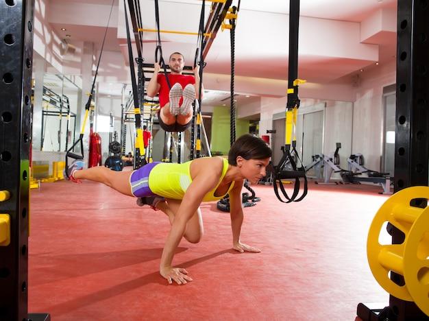 Fitness-trx-trainingsübungen an frau und mann im fitnessstudio