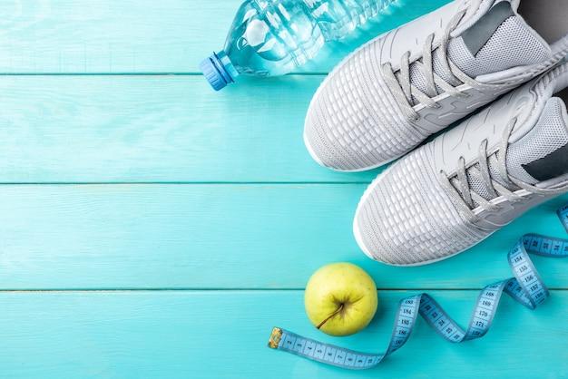 Fitness-turnschuhe, grüner apfel, maßband und flasche wasser auf blauem hölzernem hintergrund.