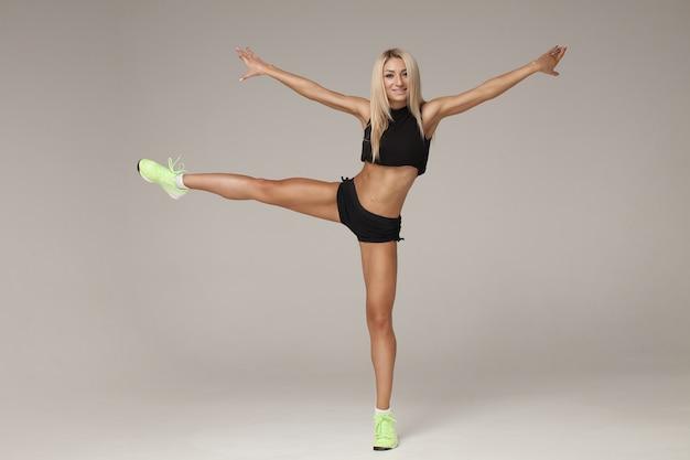Fitness- und diätkonzept - lächelndes junges mädchen im sportbekleidungstanzen