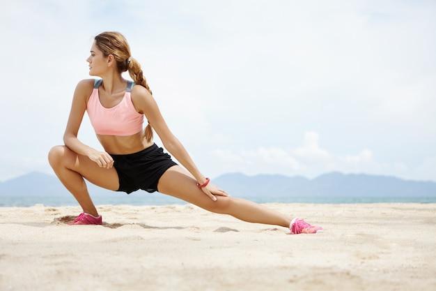 Fitness und motivation. gesundes athletenmädchen, das am strand am sonnigen tag streckt. sportliche weibliche frau mit zopf, die ihre beine aufwärmt, bevor übung im freien läuft.