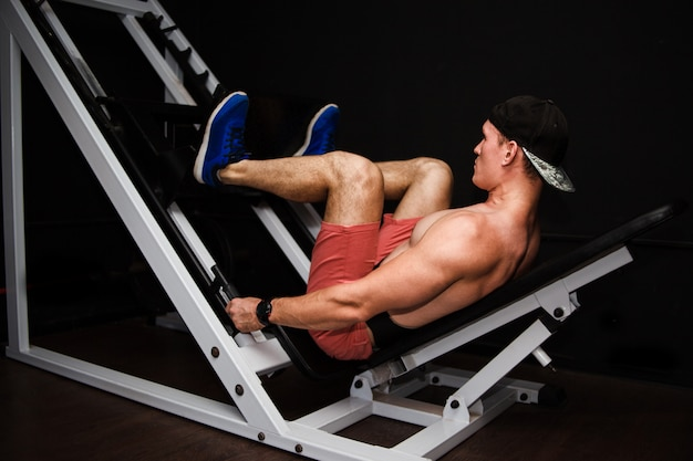 Fitness und sport. athletischer mann, der übungen auf beinen in der turnhalle tut.